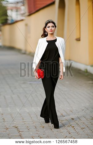 young stylish woman goes in the city with a red trendy bag. On the shoulder of the girl bag, dressed in a black Trouser suit, white jacket, bezel gemstones. Earrings, jewelry