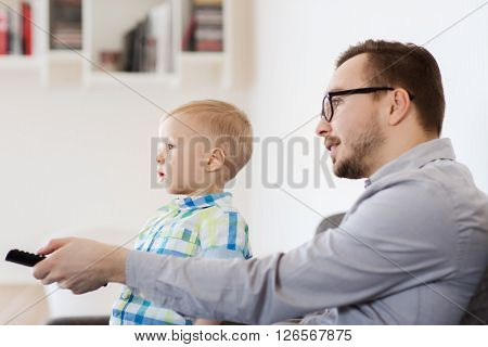 family, childhood, fatherhood, technology and people concept - happy father and little son with remote control watching tv at home