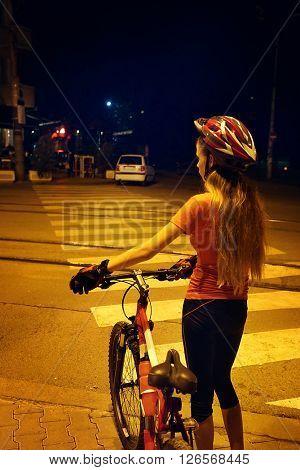 Girl is crossing  zebra crosswalk on bicycle at night city.