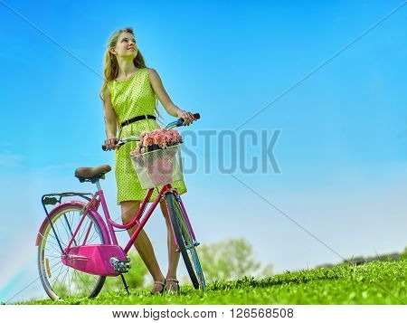 Girl wearing yellow polka dots dress rides bicycle into park.