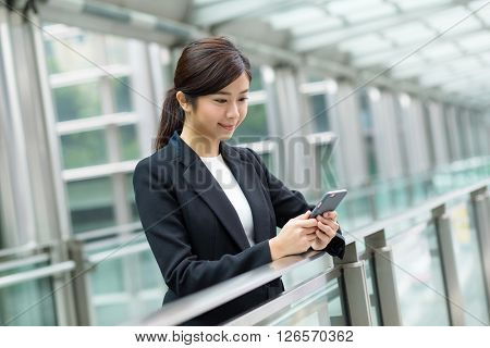 Business woman sending sms on cellphone