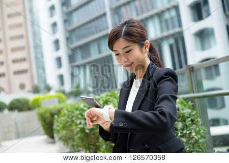 Businesswoman use of mobile phone and smart watch