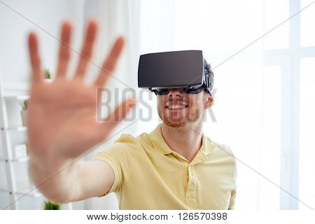technology, gaming, entertainment and people concept - happy young man with virtual reality headset or 3d glasses playing video game