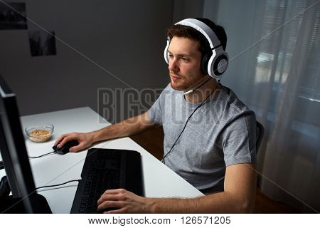 technology, gaming, entertainment, let's play and people concept - young man in headset with pc computer playing game at home and streaming playthrough or walkthrough video