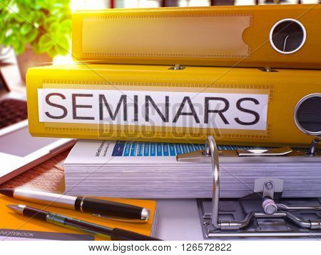 Seminars - Yellow Ring Binder on Office Desktop with Office Supplies and Modern Laptop. Seminars Business Concept on Blurred Background. Seminars - Toned Illustration. 3D Render.