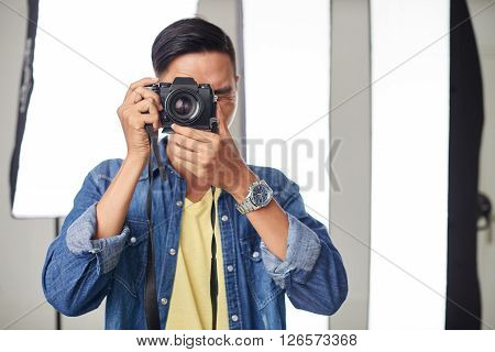 Portrait of young photographer working in photo studio