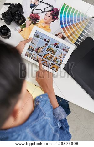 Photographer watching photos on tablet computer, view from above