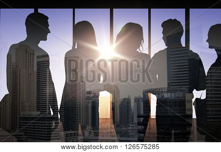 business, education and people concept - people silhouettes over double exposure office and city background