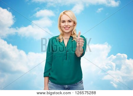 female, gender, gesture, plus size and people concept - smiling young woman in shirt and jeans showing thumbs up over blue sky and clouds background