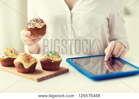 people, junk food, diet, technology and unhealthy eating concept - close up of woman with glazed cupcakes or muffins and tablet pc computer counting calories