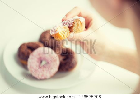 people, food, junk-food and eating concept - close up of female hand holding bitten glazed donut
