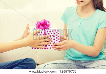 people, children, holidays, friends and friendship concept - close up of happy little girls with birthday present sitting on sofa at home