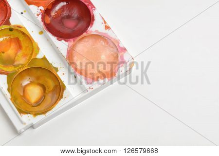 Close-up light colors of used watercolor paints isolated on white background. Art palette.