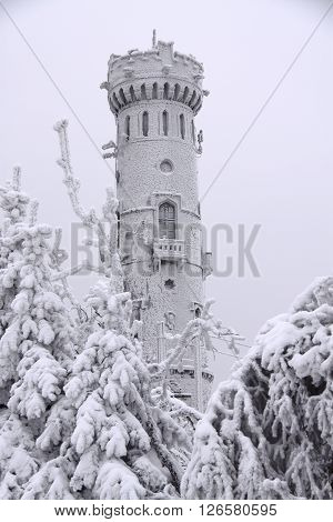 Ancient snow covered outlook tower between trees