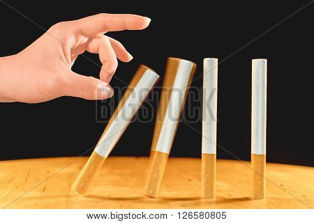 Woman's hand starting the domino of cigarettes as a concept of quit smoking.
