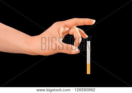 Woman trying to quit smoking by pushing it away of her isolated on black.