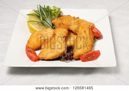 Fried chicken with tomatoes and lemon on white plate