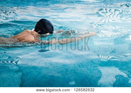 Young man in goggles and cap swimming in pool