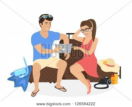 Young man and woman sitting on the luggage and using tablet pc to watch photos from their holiday or they are planning to travel and choosing the resort or hotel on tablet pc. People isolated on white