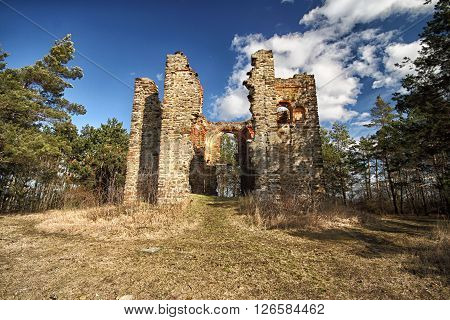 Remained walls of the ruined church on the hill in woods