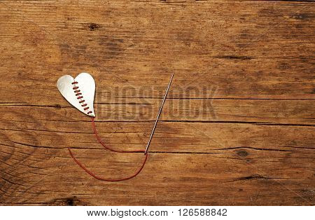 broken heart stitched with red thread on wooden table.
