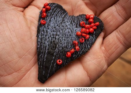 heart made of cloth with red beads on a hand concept about love at Christmas Mother's Day or Valentine's Day
