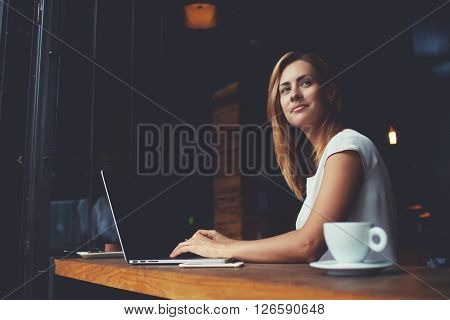 Beautiful Caucasian woman dreaming about something while sitting with portable net-book in modern cafe bar young charming female freelancer thinking about new ideas during work on laptop computer