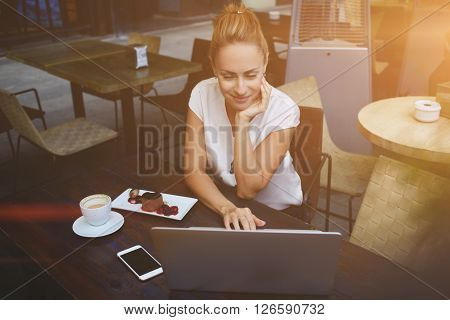 Young successful female freelancer using laptop computer for remote work while sitting in cafe bar attractive woman chatting in network via portable net-book during morning breakfast in coffee shop