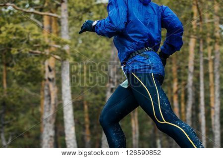 closeup of body male athlete marathon runner running race in forest in spring
