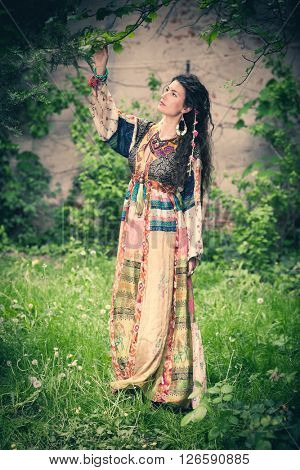 young woman in long silky boho summer dress stand in garden summer day full body shot