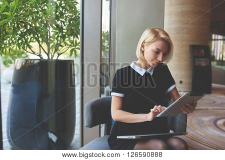 Young elegant female skilled managing director is reading e-mail on digital tablet positive feedback from the client about her work while is sitting in luxury restaurant interior during break at job