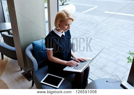 Young female is making on-line purchase via laptop computer while is sitting in modern co-working space. Businesswoman is checking e-mail in internet via portable net-book during coffee break in cafe