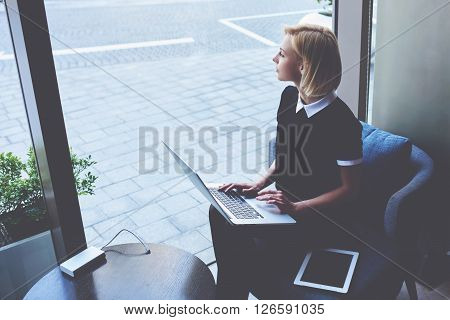 Smart woman student is thinking about something during work on coursework via portable net-book while is sitting in restaurant. Thoughtful female with laptop computer on knees is looking in window