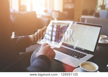 Male trader is searching information on web pages via portable digital tablet. Closeup of touch pad in man`s hand and laptop computer with copy space on the screens for your advertising text message.