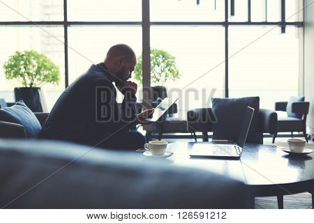 Young man government worker is exploring new bill on touch pad during coffee break in modern restaurant. Male skilled manger is reading news on website via digital tablet while is sitting in cafe