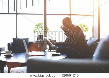 Man dealer is studying via touch pad securities before their purchase during coffee break in cafe. Male intelligent manager is drinking tea and reading something on digital tablet during rest in bar