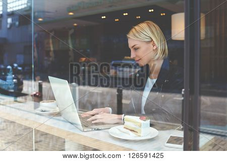 View through window of a young female student is searching needed for learning information via laptop computer before lectures in university while is sitting in modern hipster coffee shop interior