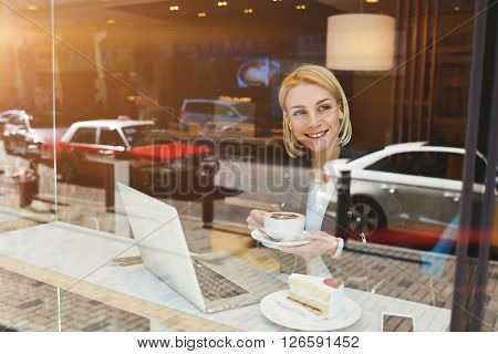 Young entrepreneur is looking satisfied while is thinking about passed business meeting while having work break in coffe shop. Thougfull female freelancer is enjoying cappuccino after work on laptop