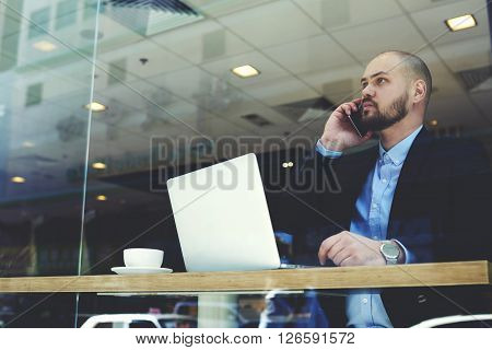 Man skilled lawyer is talking with his client via mobile phone before important court sessionwhile is sitting with laptop computer in modern interior. Serious male financier is calling with cellphone