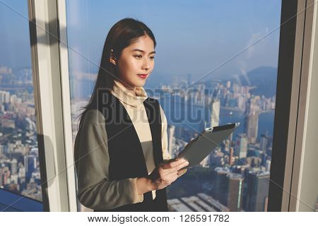Young thoughtful Asian businesswoman is holding portable touch pad while is thinking about future of the company during work break in luxury skyscraper office. Japanese female is using digital tablet