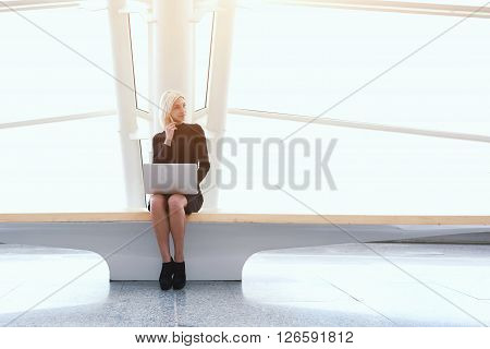 Female successful freelancer having mobile phone conversation during work on laptop computer in weekend in China. Modern woman is calling via cell telephone while is sitting with net-book in office