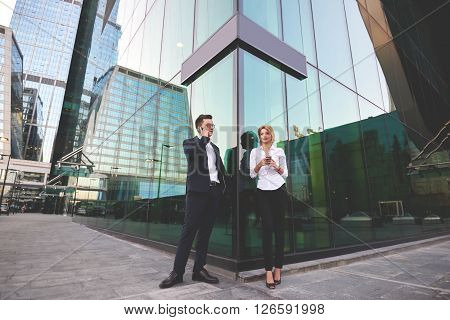 Businessman is calling via cellphone while his secretary standing near with mobile phone in hands. Two smart managers are using their cell telephones during work break while are standing outdoors
