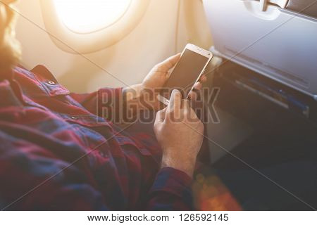 Closely image of a man`s hands is holding cell telephone with empty screen background for your advertising content. Closeup of male is watching photos on mobile phone while flying in an airplane