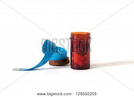 Drug Or Pills In Red Bottle With Blue Measuring Tape On Isolated White Background