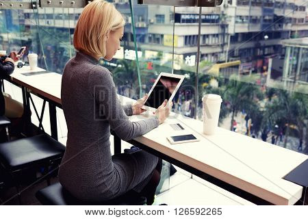 Businesswoman is reading world news on touch pad with copy space screen for your advertising text message or content. Young female is watching video on digital tablet during rest in modern coffee shop