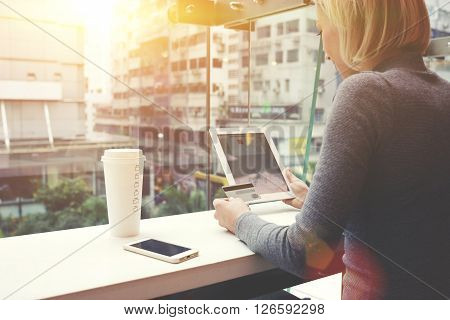 Woman is making an o-nline purchase via touch pad while is sitting in cafe with Overlooking the main street of Hong Kong. Female is using credit card for shopping in internet store via digital tablet