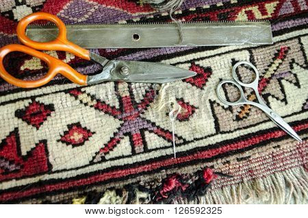 Worn old woolen carpet with scissors,a comb with needle and thread