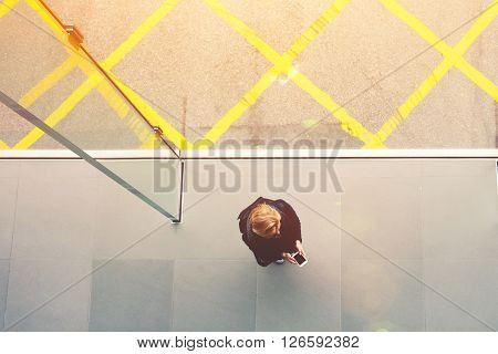 Top view of young stylish woman or student is holding mobile phone with empty screen. Blonde hipster girl with rucksack on her back is using cell telephone for navigation. Unusual shot perspective