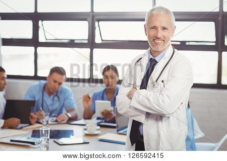 Portrait of male doctor standing with arms crossed and colleagues discussing in background