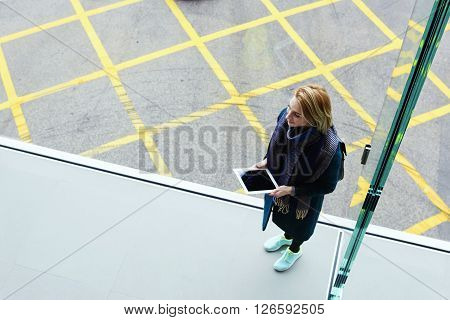 Top view of smiling trendy woman is using touch pad for navigation during her journey abroad. Hipster girl is holding digital tablet with blank copy space screen for your content. Unusual perspective